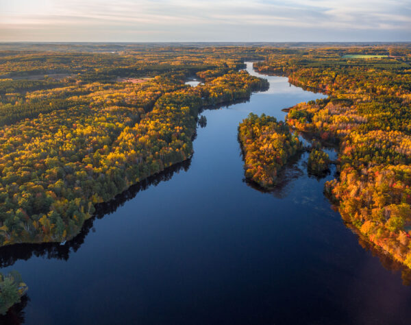 The Namekagon River stretches inth the distance as a blue ribbon. The colors of autumn trees are lit up by the sun.