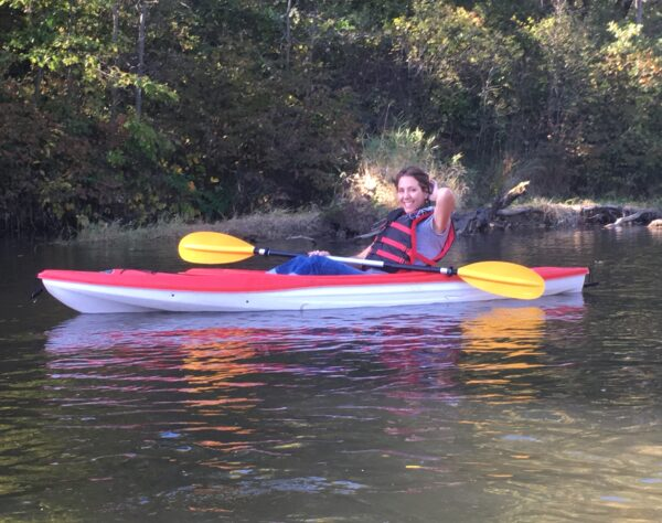 Andrea Jorgenson, Wild Rivers Conservancy Board member, smiling and sitting in a kayak with a paddle on the St. Croix River.