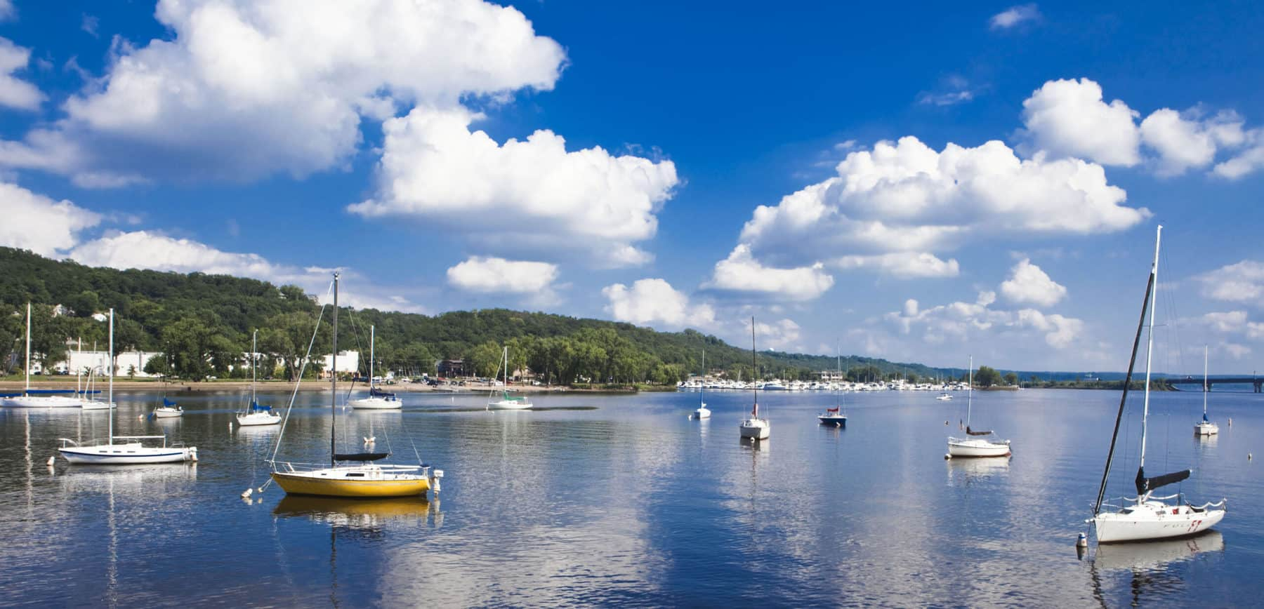 Sailboats anchored on the St. Croix River near Hudson, Wisconsin, on a sunny day with blue skies.
