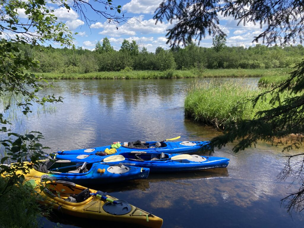 Kayaks on the riverbank of the Namekagon on a sunny dat with blue skies. Photo: conservancy Paddle Participant