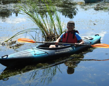Boy in a kayak smiles at the camera while holding a paddle and floating on a lake.