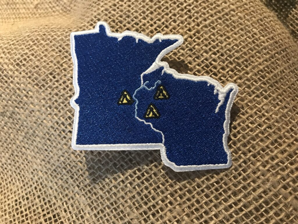 An embroidered patch with the states of Minnesota and Wisconsin is shown against a burlap backdrop. Photo by Bethany Cox.