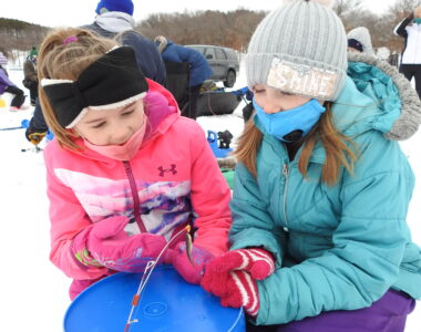 Two girls in winter jackets look at a small fish on the ice.