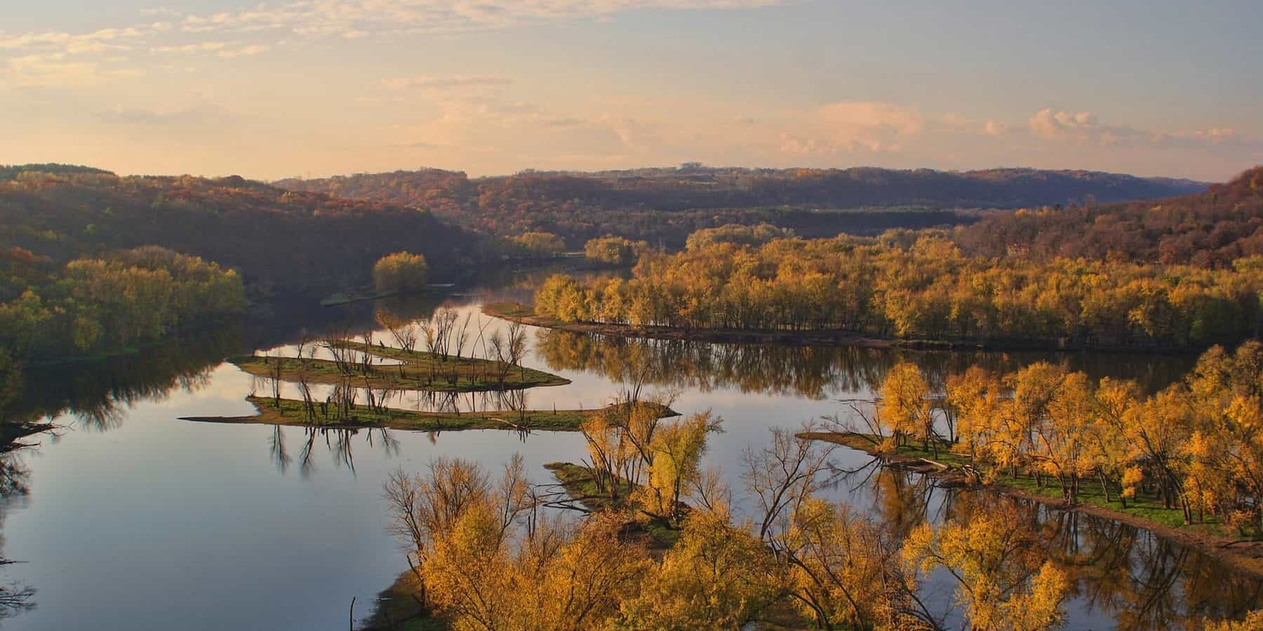 River flowing around islands on a calm autumn day with golden light over the trees.